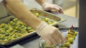 aluminium dishes : Chef catering services, disposable gloves, lays roasted snacks from baking sheet on a tray. Stock Footage