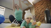 tonus : Young woman stretching hands sitting next little baby indoors. Cute lady dressed in compression shirt, gray trousers and white sneakers carefully trains without parting with small kid creeping across spacious room against background of wooden wall and mir