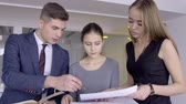 dospělí : Three young architects are discussing the project in their modern studio. The lady in black dress is showing the blueprint to her male colleague in suit, who is holding the notebook and pointing the papers with a pen. The lady is holding schemes while co-
