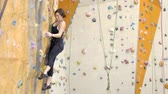 альпинист : On climbing woman is hooked on wall in gym during exercise. With an effort female sports person overcomes artificial obstacles during sports practice for courage and endurance.