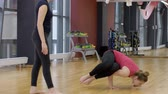 personal care : Personal trainer in yoga supports women in training on complex exercise. Fitness instructor watches as female beginner sportswoman performs stand on arms and legs during balancing Applauds when person has successfully completed. Stock Footage