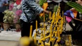 oltár : Rows of yellow slim candles, which are put into black holder ouside, close up. Candlestick is metal, black and beaten. Female tourist at the background is lighting her tool to place it near the others and colourful flags are near. Stock mozgókép