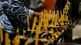 kadidlo : Closeup of Asian people putting candles in a Buddhist temple. Woman installs a yellow paraffin rod for combustion on a common altar for the fulfillment of desires. Dostupné videozáznamy