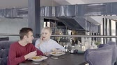 desatualizado : Lovely couple is eating salad in restaurant with stylish interior, slow motion. Blond woman in blue shirt and man in red jumper are sitting on velvet sofa at the wooden table with while plates on and talking. Vídeos