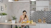 family business : Young mom with little daughter sitting at table with monitor in home kitchen, cute woman looking at laptop screen at desk with breakfast meal, holding baby in hands in bright apartment. Concept: motherhood, working, lifestyle. Stock Footage