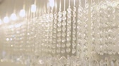 swarovski : Rows of glass decoration handing down from ceiling. Shining cristals are part of modern lamp in cozy appartment, which are lighting and rays are reflecting. Cose up.