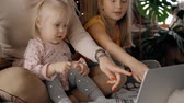 nurse : Family mom and child two baby year watching video 4g tv in computer bed a comfort clothes. mother and happy young daughter kid room home see cinema in laptop. background babysitter in apartment. Concept woman, nanny or parent lifestyle Vidéos Libres De Droits