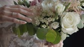 handen ineen : Bride holding bouquette on wedding ceremony. Whire roses, leafs and flowers are there in beautiful floral composition. Stockvideo