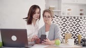 pensioner : Senior grandmother is learning payment online for shopping through smartphone. Young granddaughter is showing, teaching and pointing on phone main parts of payment be credit card by phone using internet Stock Footage