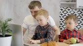 относительный : Adult and smart father spending holiday time with his two little sons. Man sitting in bright light kitchen room behind wooden desk and helping to one of his kids using modern laptop
