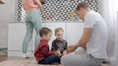 casal : Happy and adult father sitting on the floor in kitchen room and playing together with his two little sons. Woman in casual wear with little child on hands walking near her funny family