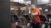 schaam : Attractive man wearing in colorful orange t-shirt and standing inside new sport gym. He using professional orbitrek for endurance improvement walking and making cardio intensity