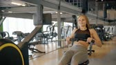 Gorgeous, nice and adorable blond hair girl wearing in trendy sport wear, training inside gym center with modern interior. She making workout on special machine for best body shape result