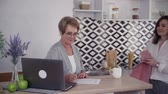 kitchen device : Mature senior woman making notes and talking on kitchen with her adult daughter. Female using laptop in modern interior room with bright light inside and spending free time at home Stock Footage