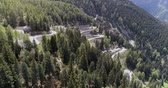 sarma : Aerial view of mountain serpentine road with trucks and cars driving on zig zag go up and down in Europe Switzerland 4K Stok Video
