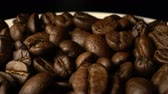 Closeup of coffee beans rotate on the table in the coffee shop and restaurant after lunch. Food and beverage advertising concept , 4k footage.