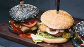 molho de carne : Three charcoal burgers are on the board, pierced with a knife, and ready to eat in 4k resolution in slow motion chamber passage