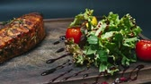 zeytinyağı : Steak with sauce, tomatoes and greens on a wooden board. Driving on a slider in 4k resolution