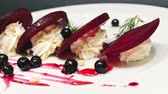 black currant : Ð¡ooking a salad from beet and whipped cream with sesame and currant sauce on a black background in 4k