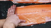 gutting : Chef takes out bones from the salmon fillet, cutting fish on slices for cooking sushi in 4k resolution in slow motion Stock Footage