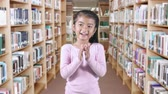 play : Happy female elementary school student standing in the library while clapping hands Stock Footage