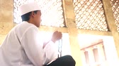 piety : Video footage of a young muslim man sitting in the Istiqlal mosque while praying to the GOD and holding a prayer beads Stock Footage
