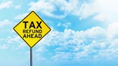 taxes due : Timelapse footage of a yellow street sign and Tax Refund Ahead text under clear sky with moving clouds Stock Footage