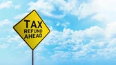 taxes due : Timelapse footage of Tax Refund Ahead text on the yellow road sign under clear sky with moving clouds Stock Footage