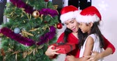 Happy young woman getting a Christmas gift from her daughter while wearing Santa hat near a Christmas tree at home, shot in 4k resolution
