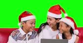 Young woman and her children using a laptop computer while wearing Santa hat and talking together on the sofa, shot in 4k resolution with green screen background Vidéos Libres De Droits