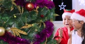 Two happy children decorating a Christmas tree together while wearing Santa hat at home, shot in 4k resolution Vidéos Libres De Droits