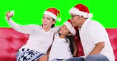 Two happy parents and their daughter celebrate Christmas day while wearing Santa hat and taking selfie photo with a smartphone on the sofa, shot in 4k resolution Vidéos Libres De Droits