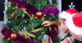 Happy little girl and her grandfather decorating a Christmas tree with ornament ball while wearing Santa hat at home, shot in 4k resolution Vidéos Libres De Droits