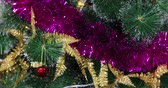 Closeup of woman hand decorating a Christmas tree with a Christmas ornament at home, shot in 4k resolution