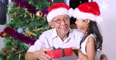 Happy grandfather wearing Santa hat and getting a Christmas gift from his granddaughter near a Christmas tree at home, shot in 4k resolution
