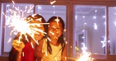 Cute little girl and her mother playing Christmas sparklers stick at night with blurred Christmas tree decoration on the background, shot in 4k resolution