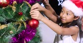 Toothless little girl and her grandfather decorate Christmas tree together while wearing Santa hat at home, shot in 4k resolution Vidéos Libres De Droits