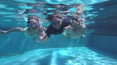 Happy young father and his children diving together while waving hands and showing thumbs up in a pool with blue water Vidéos Libres De Droits