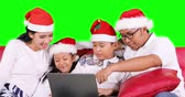 Happy family celebrate Christmas day while using a laptop computer and wearing Santa hat on the sofa, shot in 4k resolution with green screen background