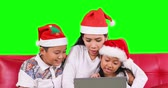 Happy family wearing Santa hat and using a laptop computer together while sitting on the sofa with green screen background, shot in 4k resolution Vidéos Libres De Droits
