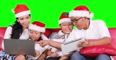 Happy family celebrate Christmas day while wearing Santa hat, using a laptop computer and digital tablet on the sofa. Shot in 4k resolution with green screen background Vidéos Libres De Droits