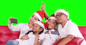 Happy family celebrate Christmas day while wearing Santa hat and taking selfie photo together with a smartphone on sofa, shot in 4k resolution with green screen background