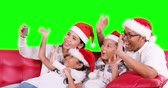Happy family celebrate Christmas day while wearing Santa hat and doing video call with a smartphone on the sofa, shot in 4k resolution with green screen background