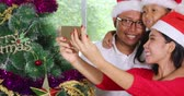 Happy family taking selfie photo with a mobile phone while wearing Santa hat near a Christmas tree at home, shot in 4k resolution Vidéos Libres De Droits