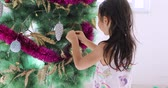 Cute toothless little girl preparing Christmas day by decorating Christmas tree with ornament, shot in 4k resolution