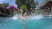 Slow motion footage of excited little boy splashing water in swimming pool while wearing goggles