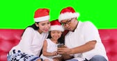 Cheerful family wearing Santa hat and using smartphone while sitting on the sofa, shot in 4k resolution with green screen background