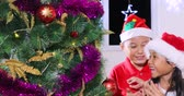 Two cheerful kids decorating a Christmas tree together while wearing Santa hat at home, shot in 4k resolution
