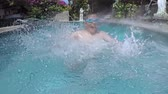 Cheerful little boy wearing goggles and splashing water in swimming pool