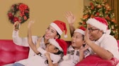 Cheerful family use a smartphone and making video call on Christmas day while wearing Santa hat on the sofa with Christmas tree background